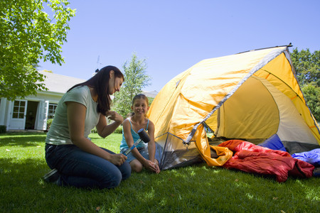 Mother and daughter setting up tent in backyard LANG_EVOIMAGES