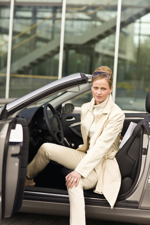 Mature adult woman sitting in convertible, Munich, Germany LANG_EVOIMAGES