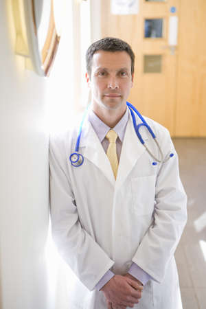 Confident doctor standing with hands clasped in corridor LANG_EVOIMAGES