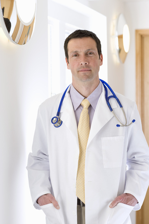 Confident doctor standing in corridor with hands in pockets of lab coat