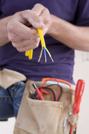Close up of electrician holding spliced wires LANG_EVOIMAGES