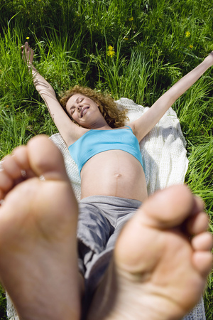 Pregnant woman relaxing in grass