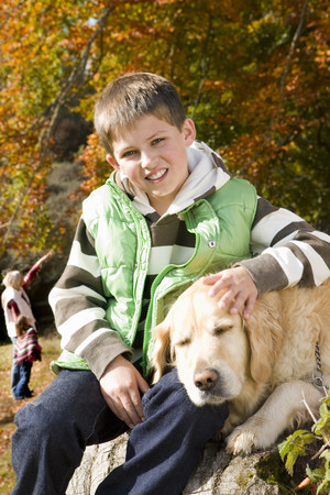 Portrait of boy and dog sitting on tree stump