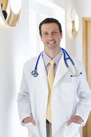 Smiling doctor standing in corridor with hands in pockets of lab coat LANG_EVOIMAGES