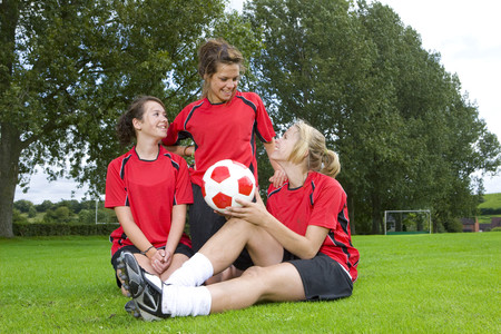 Teenage girls in soccer uniforms sitting on field LANG_EVOIMAGES