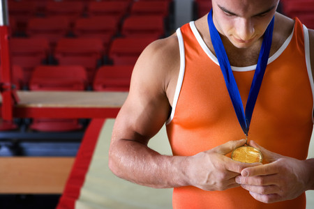 Male gymnast looking at gold medal around neck, close-up LANG_EVOIMAGES