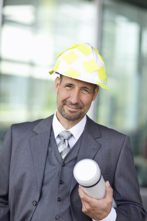 Portrait of mature man in suit wearing hardhat and holding tube container LANG_EVOIMAGES