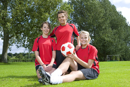 Portrait of smiling teenage girls in soccer uniforms LANG_EVOIMAGES