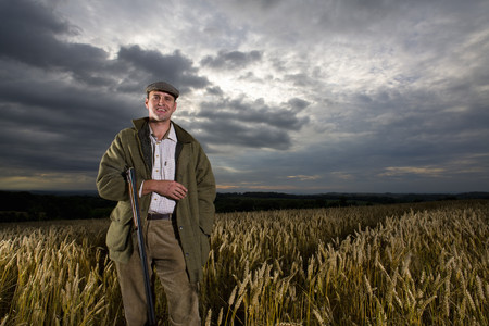 Portrait of hunter with rifle standing in wheat field LANG_EVOIMAGES