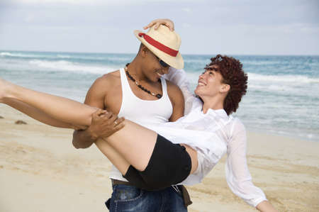 Man carrying young woman on beach, smiling, Havana, Cuba LANG_EVOIMAGES