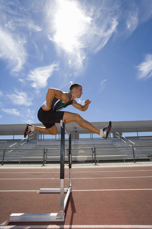 Male athlete jumping over hurdle, side view (lens flare) LANG_EVOIMAGES