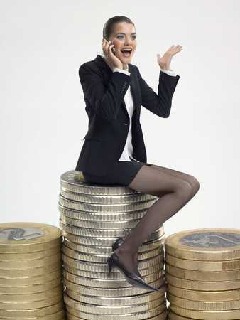 Businesswoman sitting on stack of coins LANG_EVOIMAGES