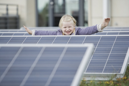 A young girl standing amongst solar panels