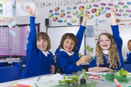 School children with arms raised with plant seedlings on desk LANG_EVOIMAGES