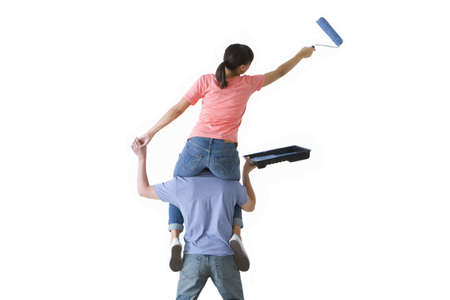 Woman on husband's shoulders painting wall