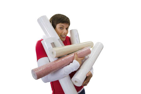 Woman trying to carry rolls of wallpaper