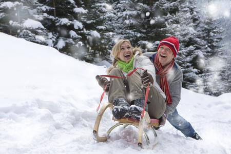Man pushing girlfriend on sled on remote snowy hillside