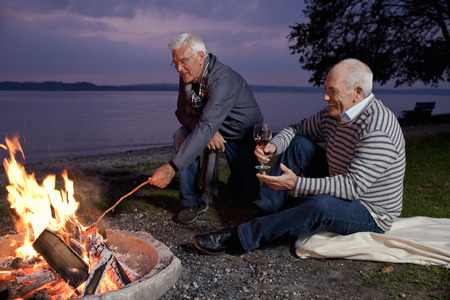 Two senior men sitting beside a campfire drinking wine