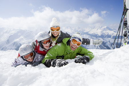 Smiling family of skiers laying in snow on ski slope