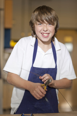 Portrait of smiling boy using pliers to cut wire in school workshop LANG_EVOIMAGES