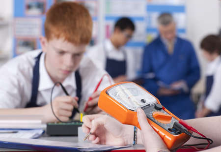 Students working on electronic device in vocational class together