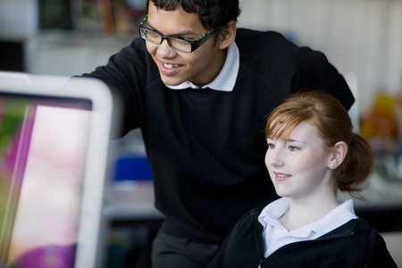 Teenage boy and girl using school computer