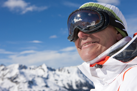 Close up of smiling man wearing ski goggles on snowy mountain
