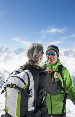 Woman fastening husbands backpack on mountain top LANG_EVOIMAGES