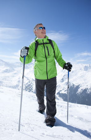 Man hiking on mountain top in snow LANG_EVOIMAGES