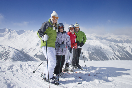 Family of skiers smiling together on mountain top LANG_EVOIMAGES