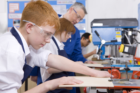 Students cutting wood in woodworking class