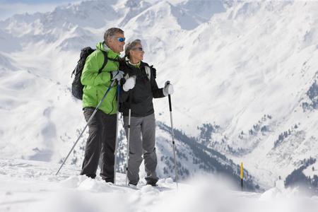 Couple hiking up ski slope on mountain