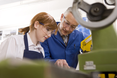 Teacher explaining to student how to use lathe in metalwork class LANG_EVOIMAGES