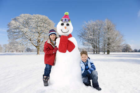 Boy and girl with snowman in sunny,snowy field