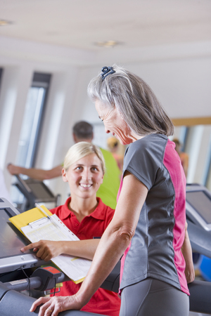 Personal trainer guiding woman on treadmill in gym