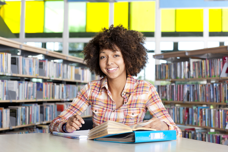 Smiling student studying in school library