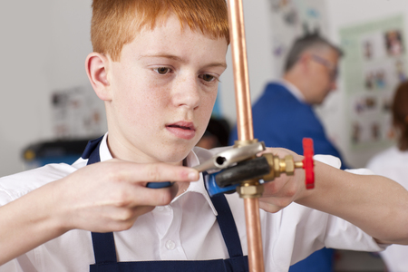 Student using wrench to tighten valve on cooper plumbing pipe LANG_EVOIMAGES