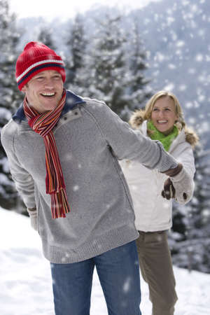 Smiling couple holding hands in snowy woods