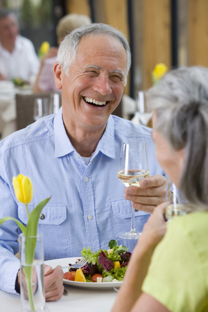 Laughing couple drinking white wine and eating salad at restaurant table
