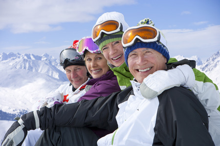 Portrait of smiling couples on snowy mountain