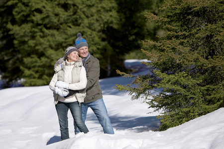Smiling couple exploring snow covered wilderness