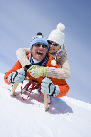 Smiling couple riding through snow on sled together LANG_EVOIMAGES