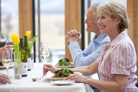 Happy couple drinking white wine and eating salad at restaurant table