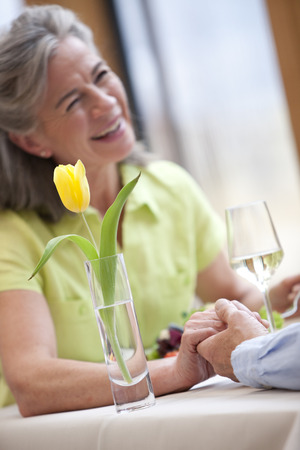 Happy couple holding hands and dining at restaurant table
