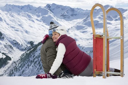 Happy senior couple with sled sitting and hugging on snowy mountain top