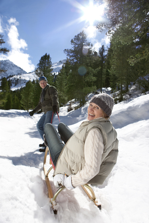 Man pulling wife on sled in snow covered wilderness