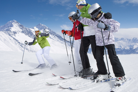 Family of skiers skiing downhill on ski slope LANG_EVOIMAGES