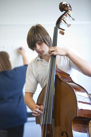 Boy practicing cello in classroom