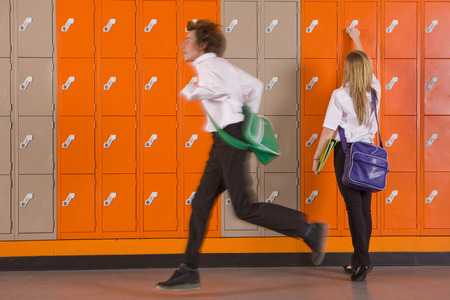 Boy rushing past student unlocking her school locker
