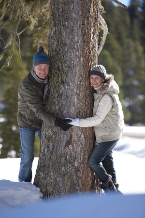 Couple holding hands around tree in snow LANG_EVOIMAGES